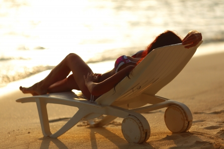 Woman in chaise-lounge relaxing on sunset beach Stock Photo - 15993583
