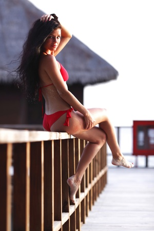 Woman in red bikini sitting on fence near tropical hotel photo