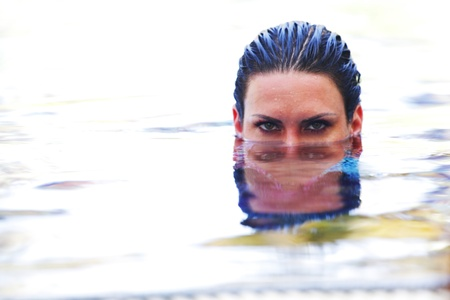 eyes hidden: Beautiful wooman ;ookin out from water in swimming pool Stock Photo