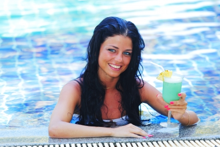 Beautiful woman in swimming pool with cocktail photo