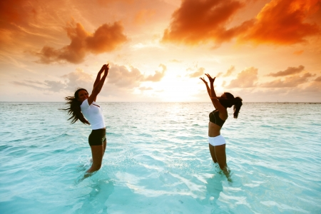 Two happy wimen playing in water on sunset Stock Photo