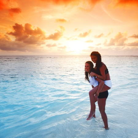 Two happy wimen playing in water on sunset photo