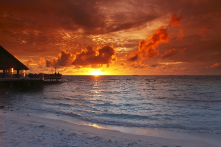 Beach and tropical resort hotel of Maldives on sunset photo