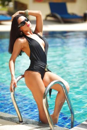 Beautiful woman posing on stairs of swimming pool Stock Photo - 15982329