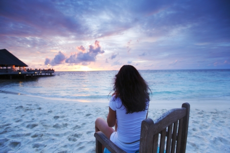 Beautiful woman enjoying sunset sitting on beach chair photo
