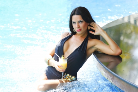 Beautiful woman with cocktail posing in swimming pool photo