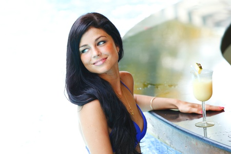 Beautiful smiling woman with cocktail in swimming pool photo