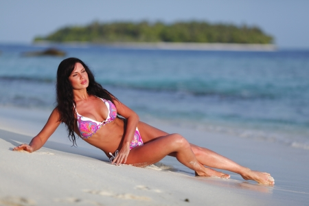 Beautiful woman in pink bikini on beach photo