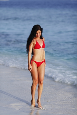 Beautiful woman in red bikini on beach photo
