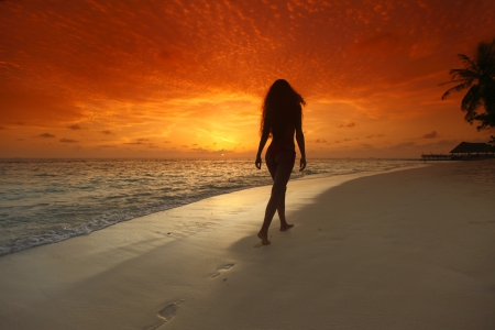 alone in the dark: Young woman walking on beach under sunset light