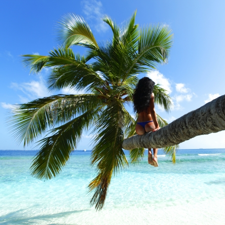 Beautiful woman sitting on palm on sea background photo