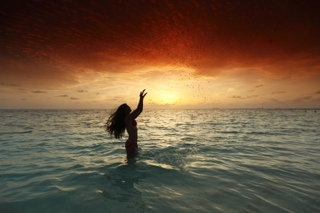 Cheerful pretty young woman splashin in sea on sunset photo