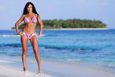 Beautiful sexy woman in bikini posing on beach photo