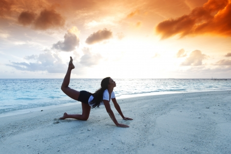 Beautiful yoga woman on beach at sunset photo