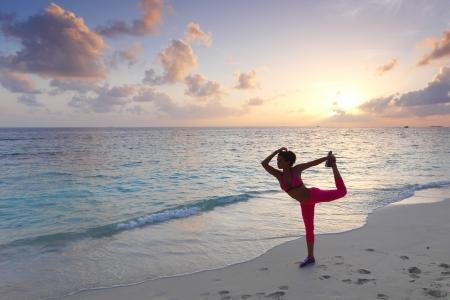 pilate: Belle femme en forme stretching sur la plage le matin Banque d'images