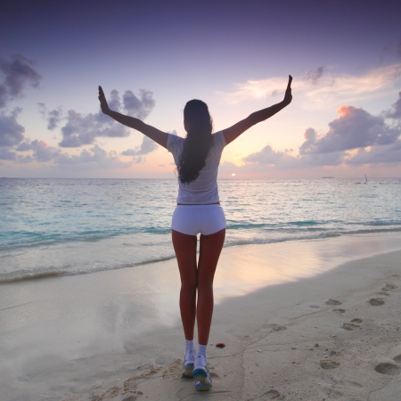 Woman in sportswear posing on beach in the morning photo