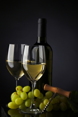 bottle with white wine and glass and grapes