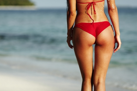 nude ass: Sexy back of a beautiful woman in red bikini on sea background Stock Photo