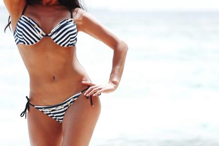 bikini model: Young sexy woman in bikini on sea background