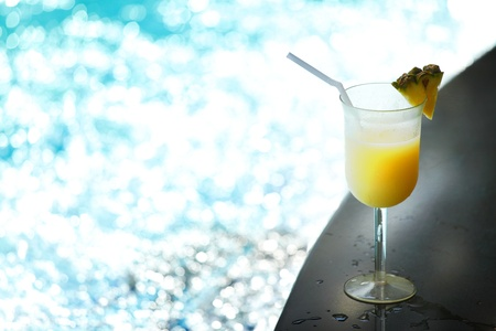 pool party: Tropical fruit alcohol cocktail near swimming pool Stock Photo