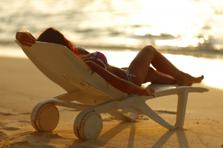 Woman in chaise-lounge relaxing on sunset beach photo