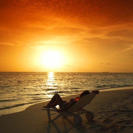 orange chairs: Woman in chaise-lounge relaxing on sunset beach