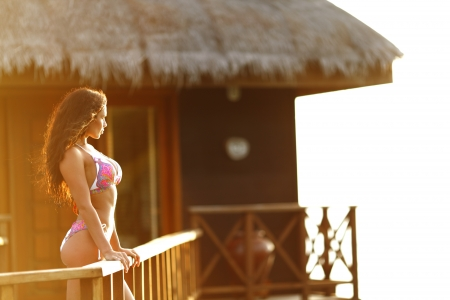 Woman standing near fence of tropical hotel Stock Photo - 16792600