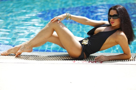 Young sexy woman sitting on the ledge of the swimming pool Stock Photo - 16380930