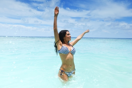 Cheerful pretty young woman splashin in sea photo