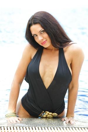 blue bikini: Beautiful brunette in swimsuit posing in wimming pool