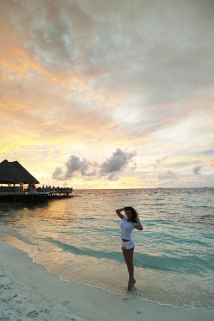Beautiful woman standing on beach at sunset Stock Photo - 16381361