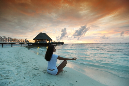 maldives beach: Yoga woman in lotus pose on beach at sunset Stock Photo
