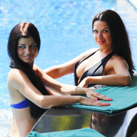 pool bar: Two beautiful women relaxing in swimming pool with cocktails Stock Photo