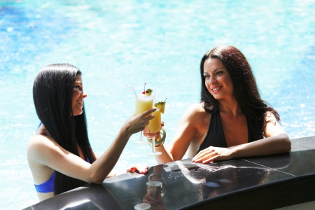 Two beautiful women relaxing in swimming pool with cocktails photo