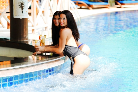 bikini pool: Two beautiful women relaxing in swimming pool with cocktails Stock Photo
