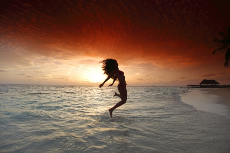 Beautiful woman jumping on beach at sunset photo