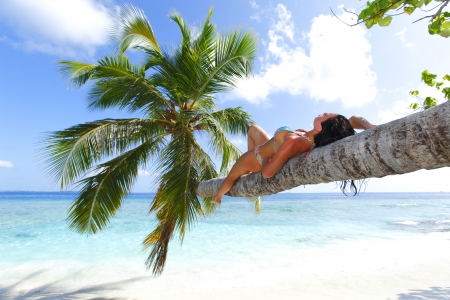 Beautiful woman lying on palm on sea background photo