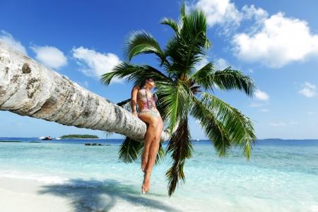 beach front: Beautiful woman sitting on palm on sea background Stock Photo