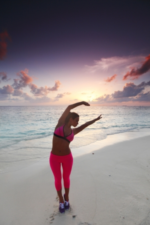 Beautiful fit woman stretching on beach in the morning photo
