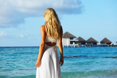 woman on tropical beach house back on the background photo