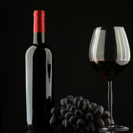 bottle with red wine and glass and grapes photo