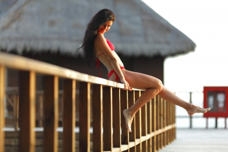 Woman in red bikini sitting on fence near tropical hotel Stock Photo - 20309649