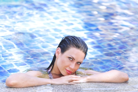 Portrait of a woman relaxing in swimming pool photo