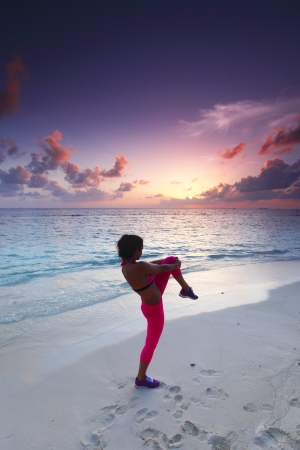 Sport fitness woman stretching on sunset beach near sea photo
