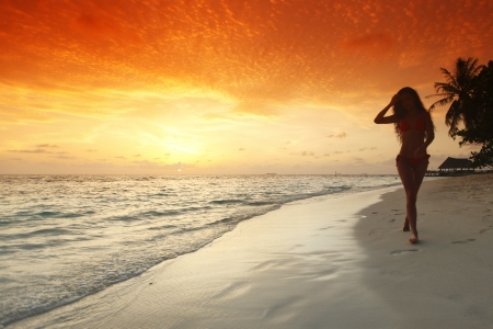 sexy woman standing: Young woman walking on beach under sunset light