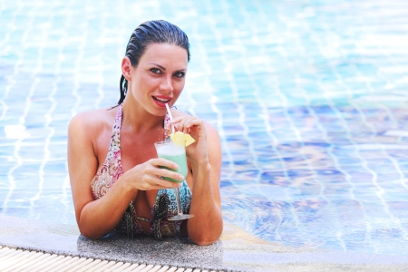 Beautiful woman in swimming pool with cocktail Stock Photo - 17409171