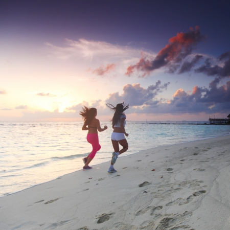 Fitness sport women running on beach at sunset photo