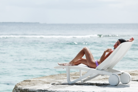 Woman lying in chaise-lounge on sea background photo