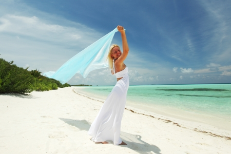 woman with a white fabric in his hands on the beach photo