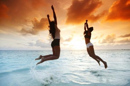 Two happy women jumping on sunset beach near sea photo